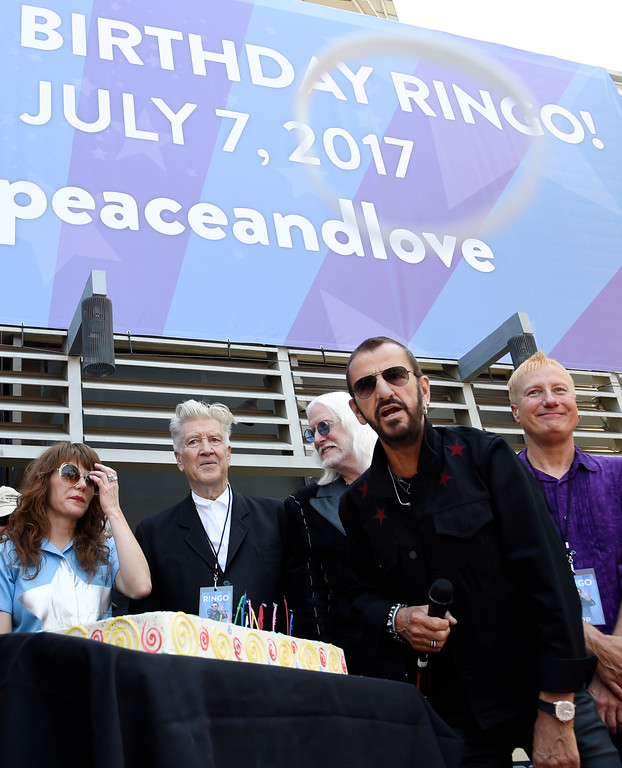 """. Ringo Starr, right, throws a bracelet with the inscription \""""Peace & Love\"""" to the crowd during a 77th birthday celebration for him at Capitol Records on Friday, July 7, 2017, in Los Angeles. In the background from left are singer Jenny Lewis, filmmaker David Lynch and musician Edgar Winter. (Photo by Chris Pizzello/Invision/AP)"""