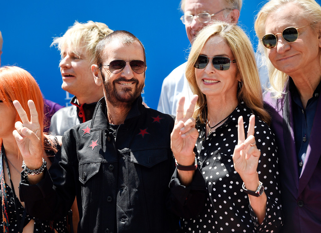 . Ringo Starr, left, poses with his wife Barbara Bach, center, and guitarist Joe Walsh, right, during a 77th birthday celebration for Starr at Capitol Records on Friday, July 7, 2017, in Los Angeles. In the background are Starr\'s son Zak Starkey, far left, and actor Ed Begley Jr. (Photo by Chris Pizzello/Invision/AP)
