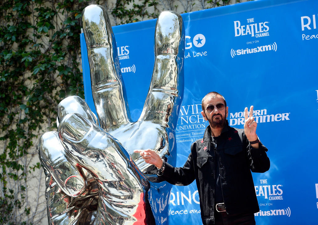 . Ringo Starr mimics a peace sign statue during a 77th birthday celebration for the former Beatle at Capitol Records on Friday, July 7, 2017, in Los Angeles. (Photo by Chris Pizzello/Invision/AP)