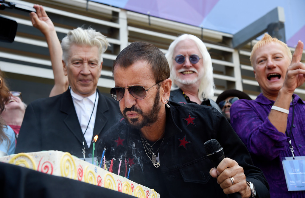 . Ringo Starr blows out candles on his birthday cake in front of guests including filmmaker David Lynch, left, and musician Edgar Winter, second from right, during a 77th birthday celebration for Starr at Capitol Records on Friday, July 7, 2017, in Los Angeles. (Photo by Chris Pizzello/Invision/AP)