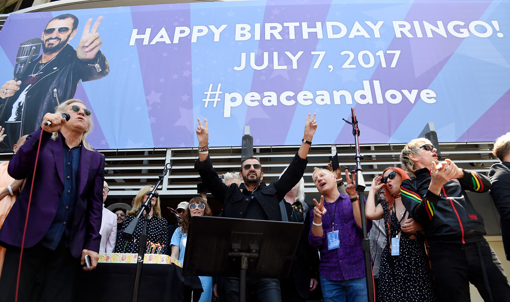 . Ringo Starr, center, is joined by guitarist Joe Walsh, far left, and other guests onstage as he celebrates his 77th birthday in front of a crowd at Capitol Records on Friday, July 7, 2017, in Los Angeles. (Photo by Chris Pizzello/Invision/AP)