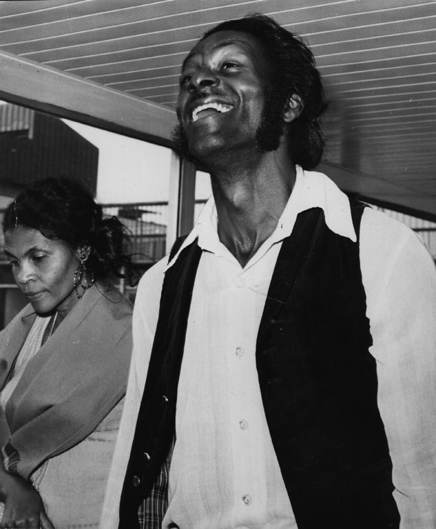 . circa 1972:  Rock \'n\' roll great Chuck Berry in good spirits at Heathrow Airport with his wife.  (Photo by Evening Standard/Getty Images)