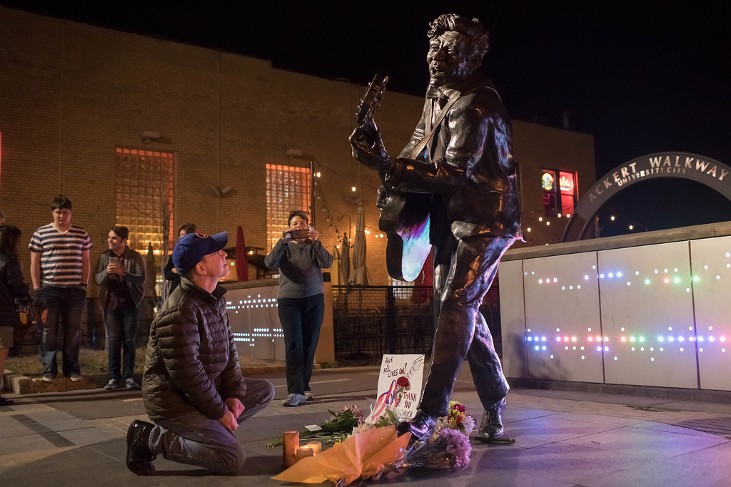 . UNIVERSITY CITY, MO - MARCH 18:  Brad Pierce lights a candle below a statue of singer and musician Chuck Berry on March 18, 2017 in University City, Missouri. The rock \'n\' roll pioneer died today at the age of 90 at his home in a suburb of St. Louis, Missouri. (Photo by Whitney Curtis/Getty Images)