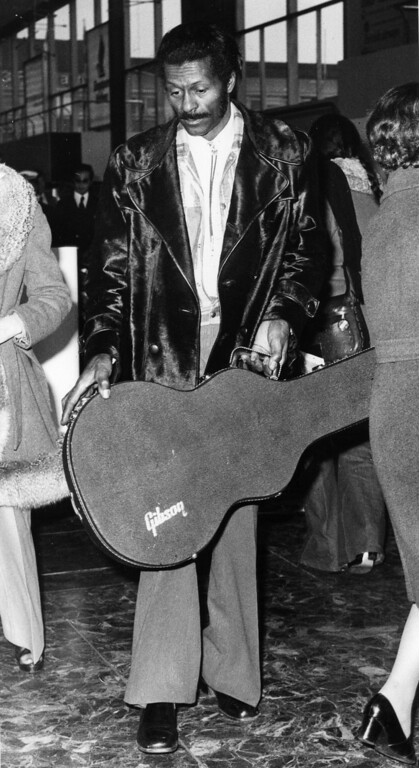 . 1st March 1975:  Rock \'n\' roll singer, songwriter and guitarist Chuck Berry at an airport holding his trademark cherry red Gibson guitar in its protective case.  (Photo by Evening Standard/Getty Images)