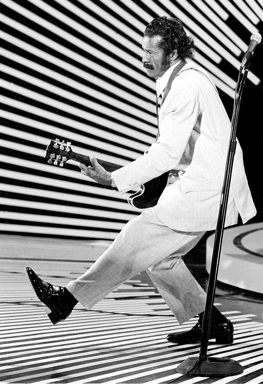 ". FILE - In this April 4, 1980 file photo, guitarist and singer Chuck Berry performs his ""duck walk\"" as he plays his guitar on stage. Berry, rock \'n\' roll\'s founding guitar hero and storyteller who defined the music\'s joy and rebellion in such classics as \""Johnny B. Goode,\"" \'\'Sweet Little Sixteen\"" and \""Roll Over Beethoven,\"" died Saturday, March 18, 2017, at his home west of St. Louis. He was 90. (AP Photo)"