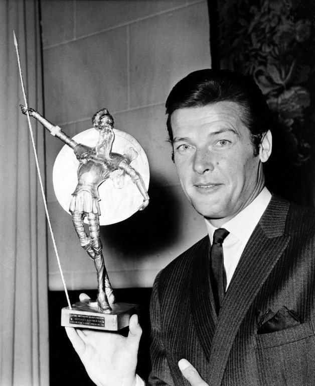 """. FILE - This is a  July 8, 1968  file photo of British actor Roger Moore  as he poses with Spain\'s most prized award, the Don Quixote Award, which was presented to him at the Spanish Embassy in London,  The award, an equivalent to Hollywood\'s Oscar, was awarded to him for his role in the British series \""""The Saint,\"""" one of the most popular shows on Spanish TV.  Roger Moore\'s family said Tuesday May 23, 2017 that the  former James Bond star has died after a short battle with cancer (AP Photo/ File)"""