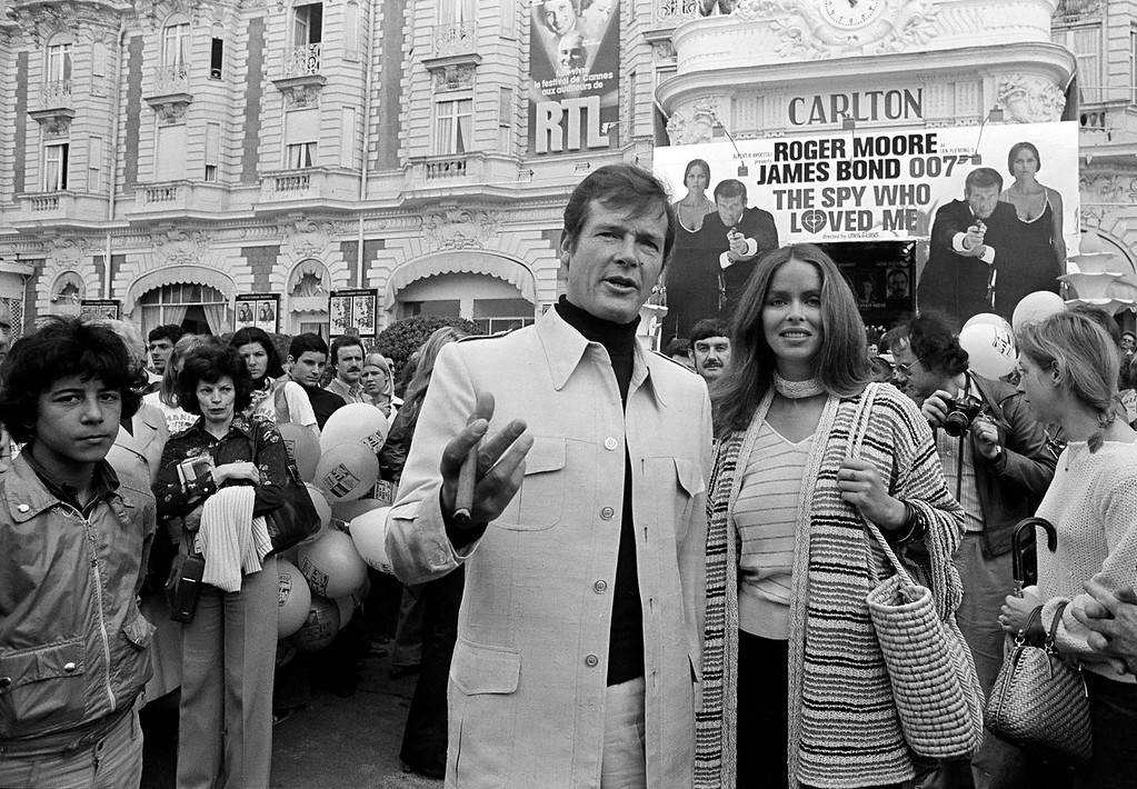 """. FILE - In this May 20, 1977 file photo, actor Roger Moore, alias British secret agent James Bond, is accompanied by co-star Barbara Bach as they arrive for the screening of their latest 007 feature, \""""The Spy Who Loved Me,\"""" during the Cannes Film Festival at the French Riviera. Moore, played Bond in seven films, more than any other actor.  Roger Moore\'s family said Tuesday May 23, 2017 that the  former James Bond star has died after a short battle with cancer  (AP Photo, File)"""