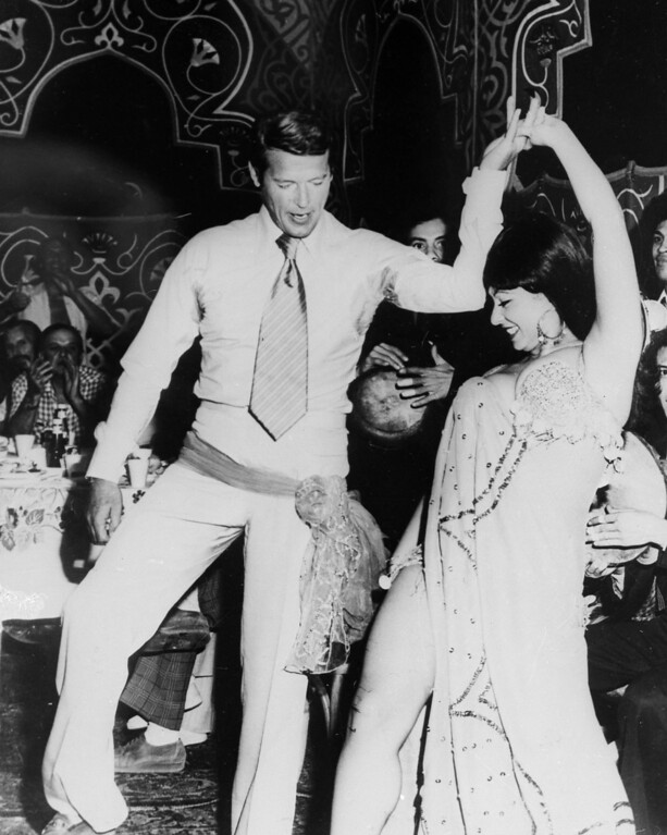 """. Roger Moore, star of the latest James Bond film \""""The Spy Who Loved Me\"""" celebrates his 49th birthday at the base of the Great Pyramids in Egypt with belly dancer Nadia Fouad, Nov. 1976.  (AP Photo)"""