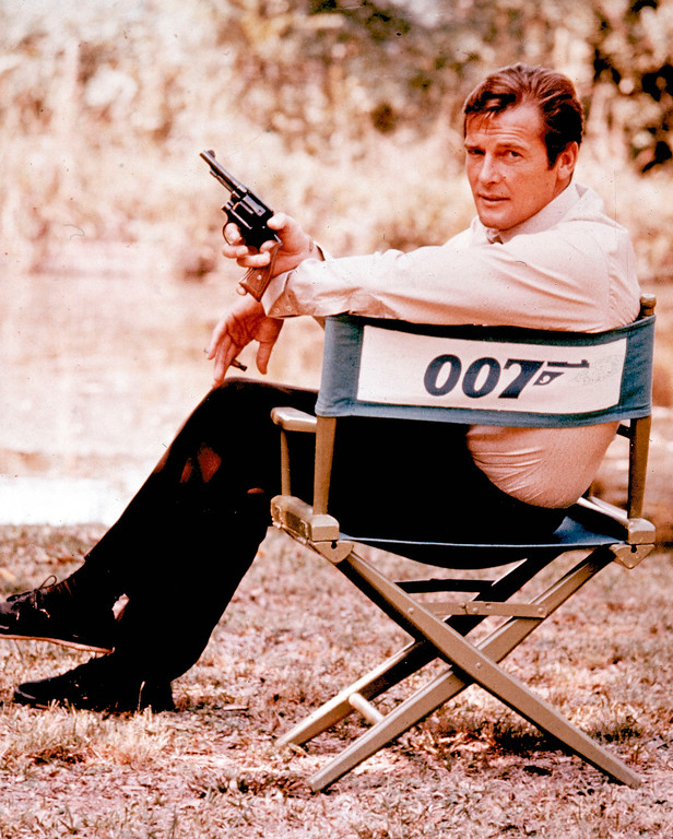 . FILE - British actor Roger Moore, playing the title role of secret service agent 007, James Bond, is shown on location in England in 1972. Moore, played Bond in seven films, more than any other actor.  Roger Moore\'s family said Tuesday May 23, 2017 that the  former James Bond star has died after a short battle with cancer  (AP Photo, File)