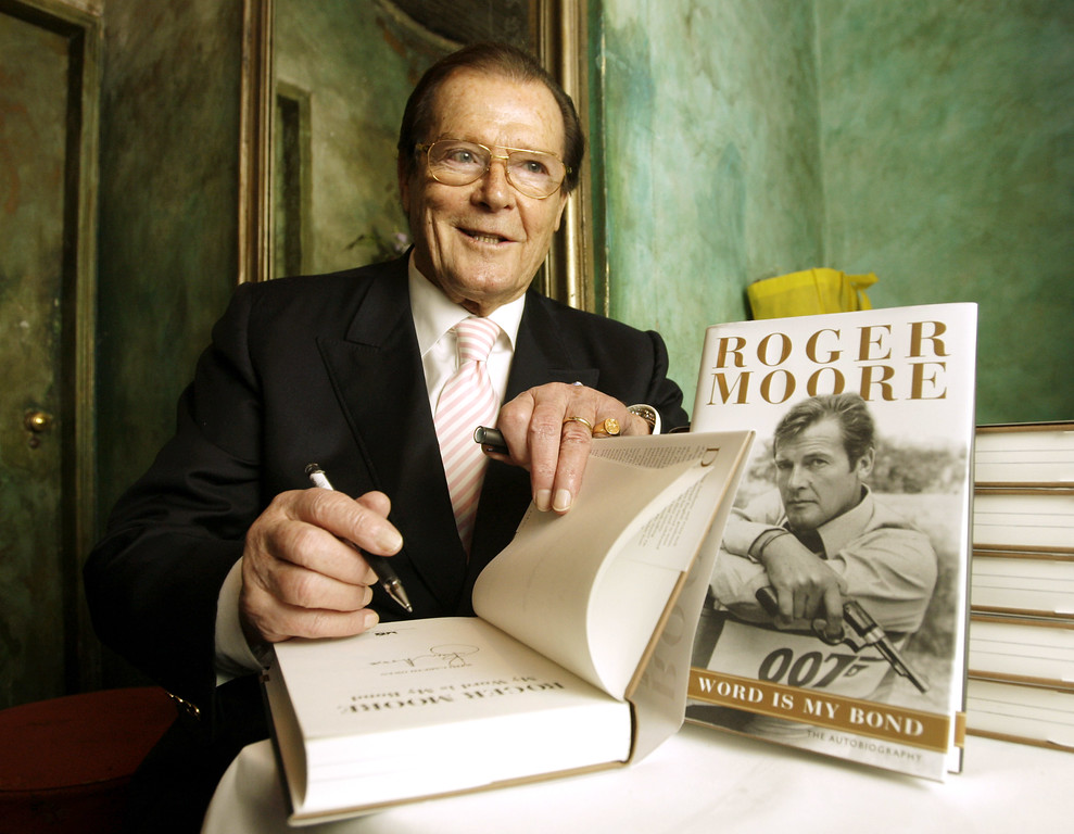 """. British actor Roger Moore signs autograph on his latest book \""""The World is My Bond\"""" during the news conference in Hong Kong Thursday, Nov. 27, 2008.  (AP Photo/Kin Cheung)"""