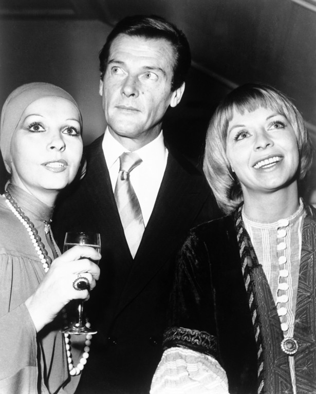 . British actor Roger Moore, his wife Luise, left, and his new leading lady Susannah York, who is starring with the actor in the new film comedy �Heaven Save Us from Our Friends,� which is now being made at Pinewood Studious with locations in Belgium. They were having a New Year drink on Jan. 2, 1975 at London�s Garrick Club, England, as guests of Producer Dimitri de Grunwald, unseen. (AP Photo/Dear)