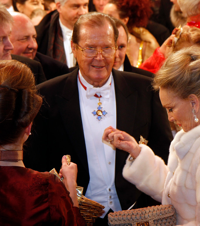 . British actor Sir Roger Moore arrives for the traditional Opera Ball in front of the state opera in Vienna, Austria on Thursday Feb. 16, 2012. (AP Photo/Ronald Zak)