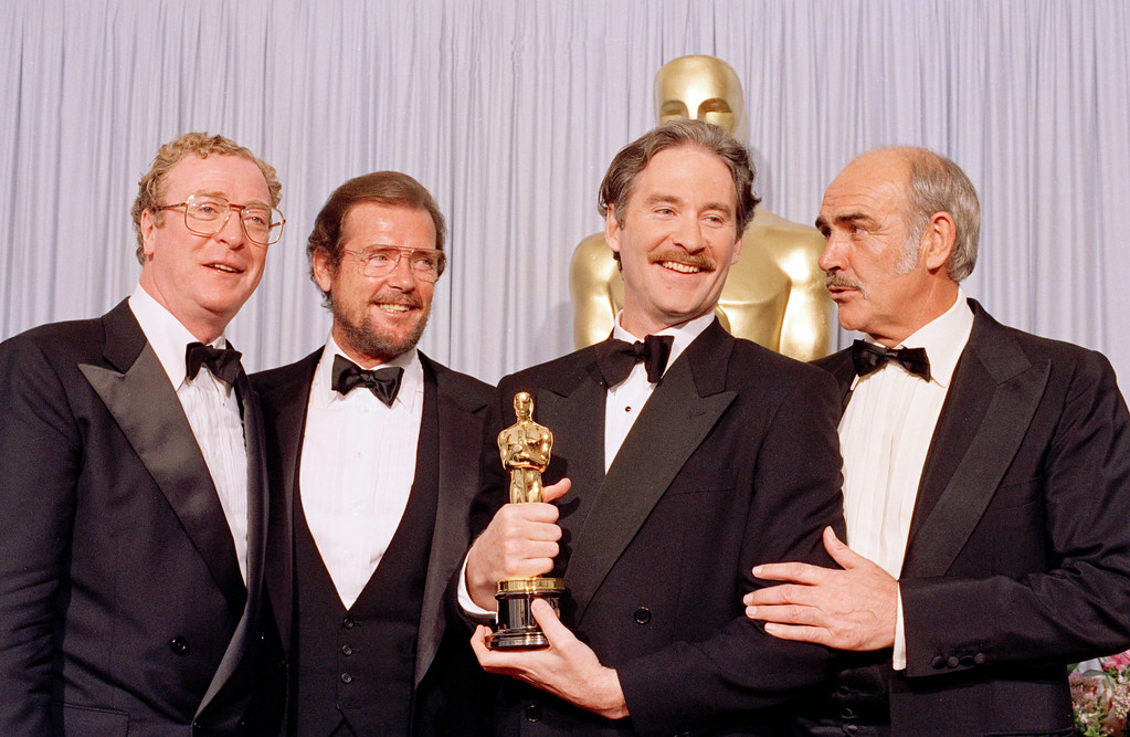""". File - Actor Kevin Kline, second from right, is flanked by actors and presenters, from left, Michael Caine, Roger Moore and Sean Connery after Kline was honored as best supporting actor for his role in \""""A Fish Called Wanda,\"""" at the 61st annual Academy Awards in Los Angeles, March 29, 1989.  Moore, played Bond in seven films, more than any other actor.  Roger Moore\'s family said Tuesday May 23, 2017 that the  former James Bond star has died after a short battle with cancer. (AP Photo/Lennox McLendon)"""