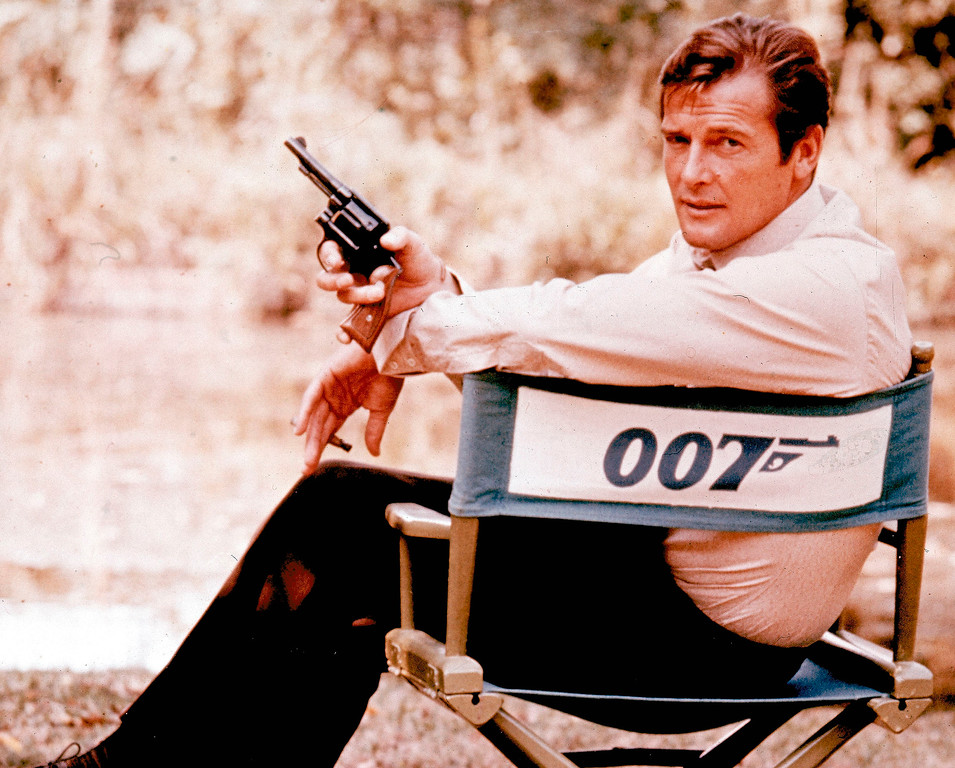 . FILE - British actor Roger Moore, playing the title role of secret service agent 007, James Bond, is shown on location in England in 1972. Moore, played Bond in seven films, more than any other actor.  Roger Moore\'s family said Tuesday May 23, 2017 that the  former James Bond star has died after a short battle with cancer.  (AP Photo, File)