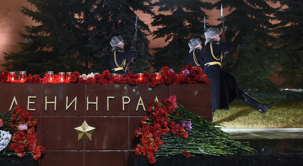 ". Flowers in memory of victims of the blast in the Saint Petersburg metro are seen at a memorial stone reading Leningrad by the Kremlin wall as honour guard soldiers march during the changing of the guards ceremony in central Moscow on April 3, 2017. Russia opened a probe into a suspected ""act of terror\"" Monday after 10 people were killed and dozens more injured in a blast that rocked the Saint Petersburg metro. (VASILY MAXIMOV/AFP/Getty Images)"