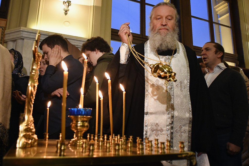 ". An Orthodox priest leads a service in memory of victims of the blast in the Saint Petersburg metro in a chapel at Leningradsky railway station in Moscow on April 3, 2017. Russia opened a probe into a suspected ""act of terror\"" Monday after 10 people were killed and dozens more injured in a blast that rocked the Saint Petersburg metro. (ALEXANDER NEMENOV/AFP/Getty Images)"