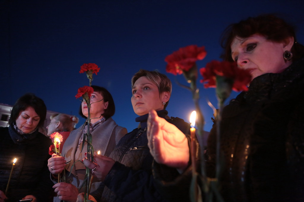 ". Women hold flowers and lit candles as they take part in a gathering in memory of victims of the blast in the Saint Petersburg metro in Simferopol, Crimea, on April 3, 2017. Ten people were killed and several more injured Monday after an explosion rocked the metro system in Russia\'s second city Saint Petersburg, and authorities launched a probe into suspected ""act of terror\"". (MAX VETROV/AFP/Getty Images)"