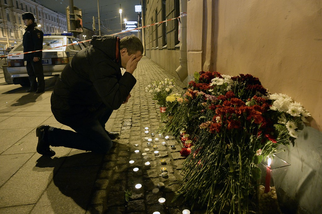 ". A man reacts as he places flowers in memory of victims of the blast in the Saint Petersburg metro outside Technological Institute station on April 3, 2017. Ten people were killed and several more injured Monday after an explosion rocked the metro system in Russia\'s second city Saint Petersburg, and authorities launched a probe into suspected ""act of terror\"". (OLGA MALTSEVA/AFP/Getty Images)"