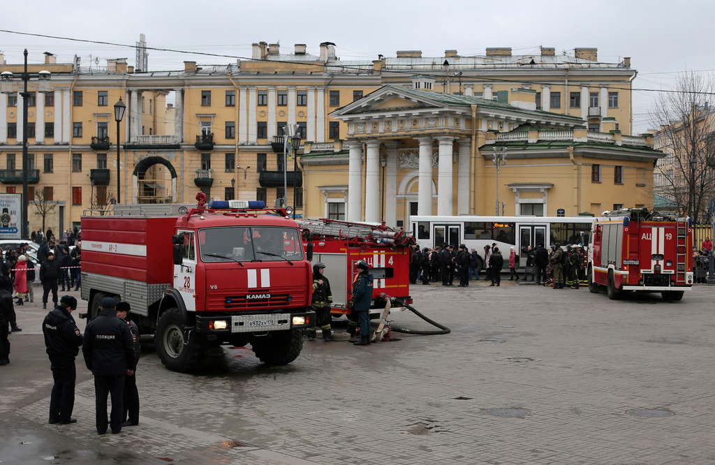 . Russian police and emergency service officers stand near fire trucks at Sadovaya square in St. Petersburg, Russia, Monday, April 3, 2017.  The subway in the Russian city of St. Petersburg is reporting that there are fatalities and several people have been injured in an explosion on a subway train. (AP Photo/Evgenii Kurskov)