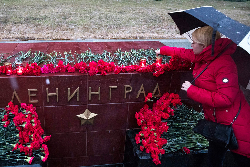 . A woman lights a candle in memory of victims killed by a bomb blast in a subway train in St. Petersburg at the memorial stone with the word Leningrad (St. Petersburg) at the Tomb of Unknown Soldier in front of the Kremlin wall in Moscow, Russia, Monday, April 3, 2017. A bomb blast tore through a subway train in Russia\'s second-largest city Monday, killing 10 people and injuring about 40 as President Vladimir Putin visited the city, authorities said. (AP Photo/Pavel Golovkin)