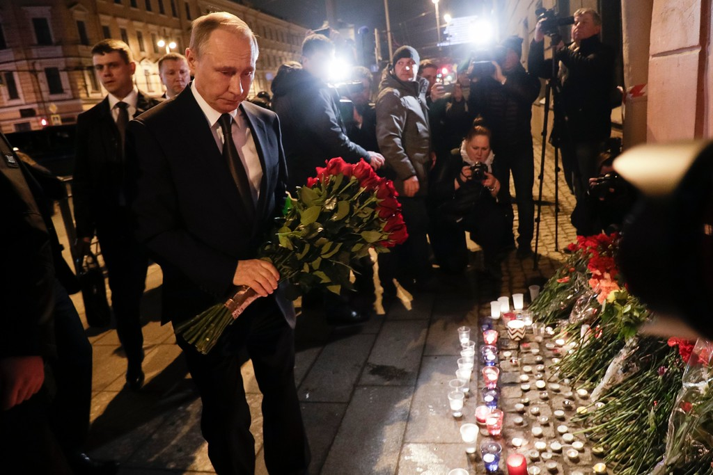 . Russian President Vladimir Putin, left, lays flowers at a place near the Tekhnologichesky Institut subway station in St.Petersburg, Russia, Monday, April 3, 2017. A bomb blast tore through a subway train deep under Russia\'s second-largest city Monday, killing several people and wounding many more in a chaotic scene that left victims sprawled on a smoky platform. (AP Photo/Dmitri Lovetsky)