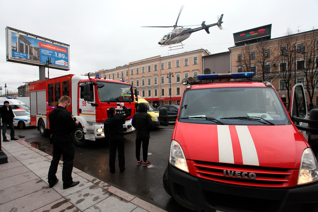 . A helicopter flies over the fire trucks after an explosion at Tekhnologichesky Institut subway station in St.Petersburg, Russia, Monday, April 3, 2017.  The subway in the Russian city of St. Petersburg is reporting that there are fatalities and several people have been injured in an explosion on a subway train. (Alexander Tarasenkov/Interpress via AP)