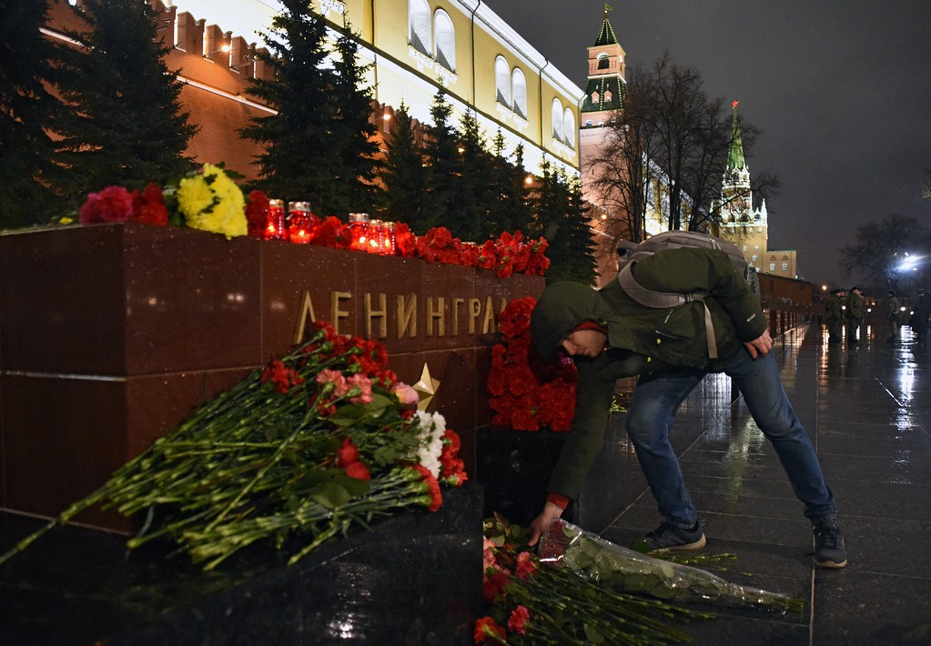 ". A man lays flowers in memory of victims of the blast in the Saint Petersburg metro at a memorial stone reading Leningrad by the Kremlin wall in central Moscow on April 3, 2017. Russia opened a probe into a suspected ""act of terror\"" Monday after 10 people were killed and dozens more injured in a blast that rocked the Saint Petersburg metro. (VASILY MAXIMOV/AFP/Getty Images)"