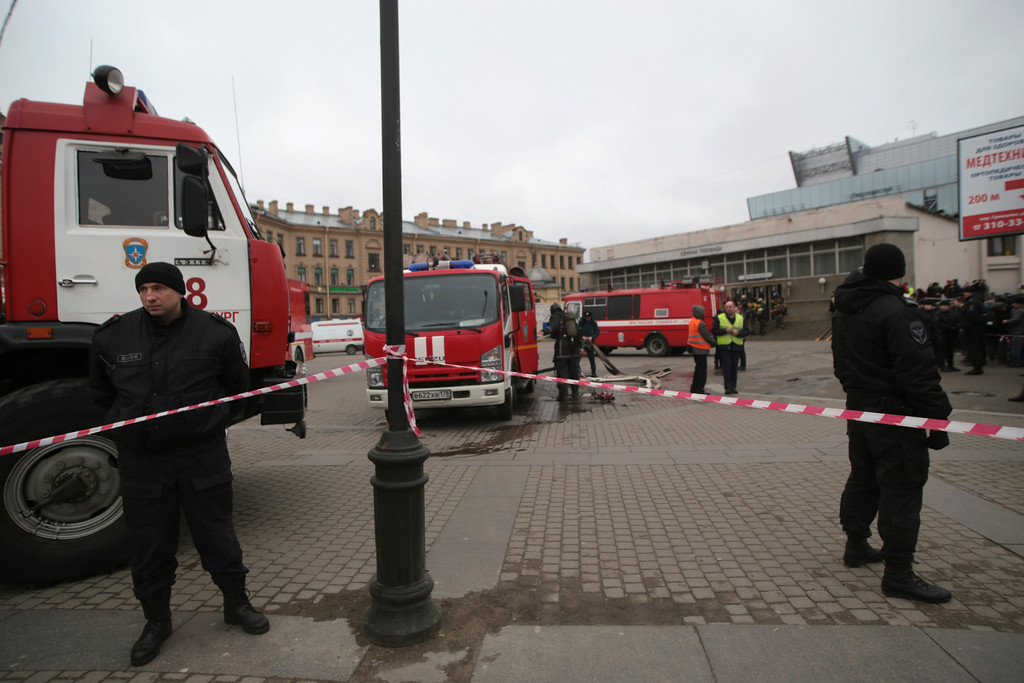 . Russian police and emergency service officers stand near fire trucks near the entrance of Sennaya Square subway station in St. Petersburg, Russia, Monday, April 3, 2017. The subway in the Russian city of St. Petersburg is reporting that there are fatalities and several people have been injured in an explosion on a subway train. (AP Photo/Evgenii Kurskov)