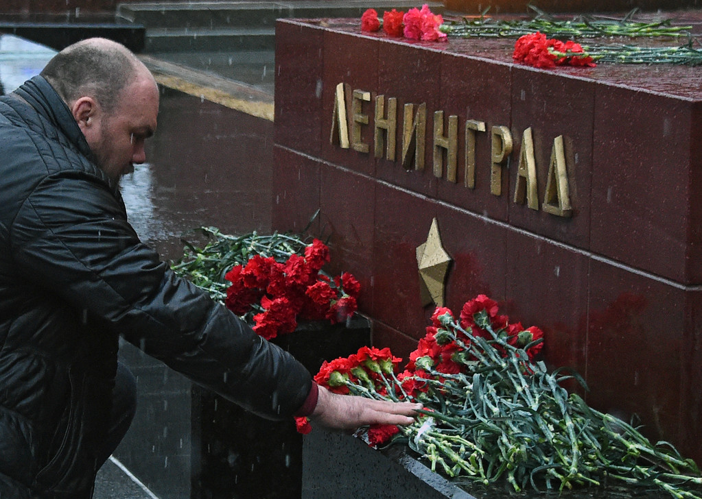 ". A man lays flowers in memory of victims of the blast in the Saint Petersburg metro at a memorial stone reading Leningrad by the Kremlin wall in central Moscow on April 3, 2017. Ten people were killed and several more injured Monday after an explosion rocked the metro system in Russia\'s second city Saint Petersburg, and authorities launched a probe into suspected ""act of terror\"". (VASILY MAXIMOV/AFP/Getty Images)"
