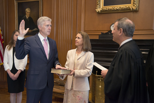 . WASHINGTON, DC - APRIL 10: Chief Justice John G. Roberts, Jr., administered the Constitutional Oath to the Honorable Neil M. Gorsuch as his wife Marie Louise Gorsuch holds the Bible in a private ceremony attended by the Justices of the Supreme Court and members of the Gorsuch family in the Justices Conference Room at the Supreme Court Building on April 10, 2017 in Washington, DC. Gorsuch is the 113th Supreme Court justice. (Photo by Franz Jantzen/Supreme Court of the United States via Getty Images)