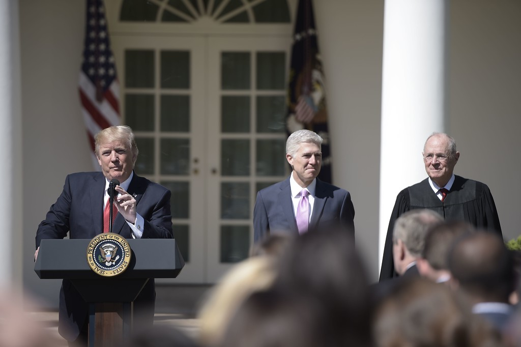 . US President Donald Trump speaks as Justice Anthony Kennedy (R) and Neil Gorsuch (C) look on following Gorsuch\'s swearing-in as an associate justice of the US Supreme Court earlier in a private ceremony, on April 10, 2017 in the Rose Garden of the White House  in Washington, DC.   / AFP PHOTO / Brendan SMIALOWSKI        (Photo credit should read BRENDAN SMIALOWSKI/AFP/Getty Images)