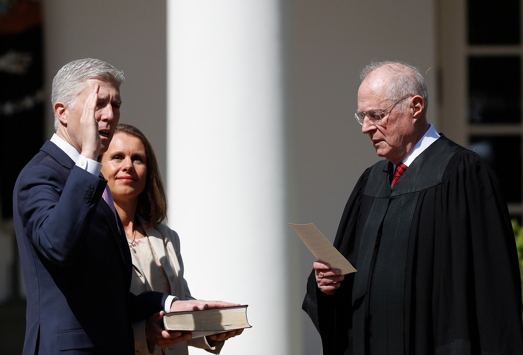 . Supreme Court Justice Anthony Kennedy administers the judicial oath to Justice Neil Gorsuch during a re-enactment in the Rose Garden of the White House White House in Washington, Monday, April 10, 2017. Holding the bible is Gorsuch\'s wife Marie Louise Gorsuch. (AP Photo/Carolyn Kaster)