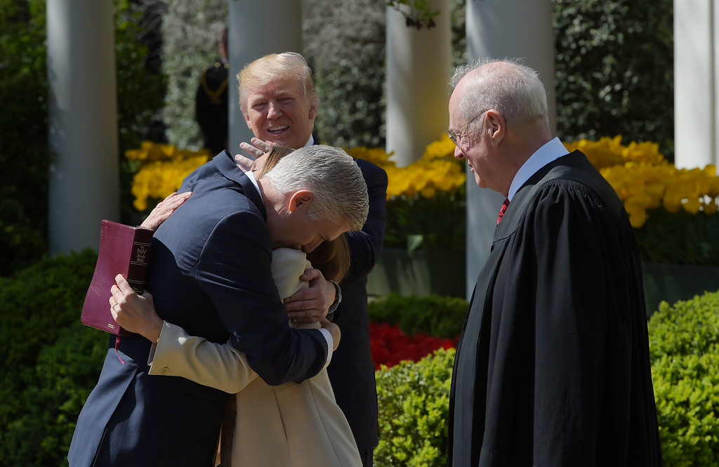 . US President Donald Trump watches as Justice after Anthony Kennedy administered the oath of office to Neil Gorsuch as an associate justice of the US Supreme Court,as Gorsuch hugs his wife Louise, in the Rose Garden of the White House on April 10, 2017 in Washington, DC.   / AFP PHOTO / Mandel NGAN        (Photo credit should read MANDEL NGAN/AFP/Getty Images)