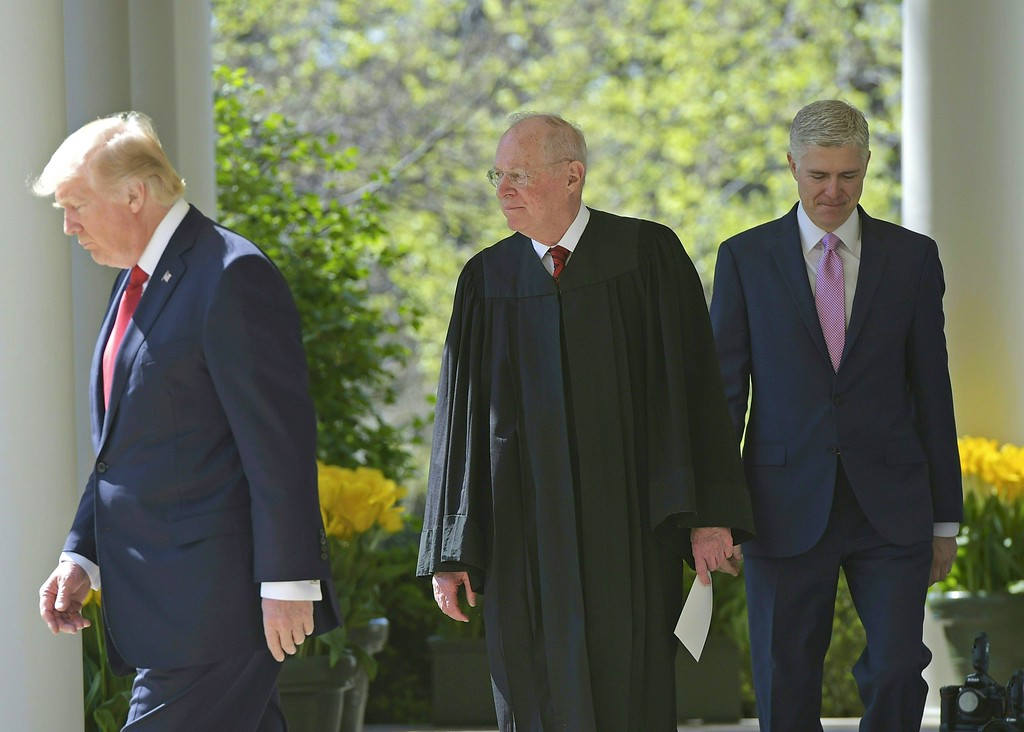 . US President Donald Trump leads the way (L) in front of Justice Anthony Kennedy (C) and Neil Gorsuch (C) moments before Gorsuch\'s swearing-in as an associate justice of the US Supreme Court on April 10, 2017 in the Rose Garden of the White House  in Washington, DC.   / AFP PHOTO / Mandel NGAN        (Photo credit should read MANDEL NGAN/AFP/Getty Images)