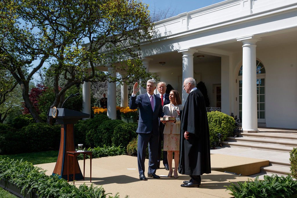 . President Donald Trump watches as Supreme Court Justice Anthony Kennedy administers the judicial oath to Judge Neil Gorsuch, accompanied by his wife Marie Louise, during a re-enactment in the Rose Garden of the White House in Washington, Monday, April 10, 2017. (AP Photo/Evan Vucci)
