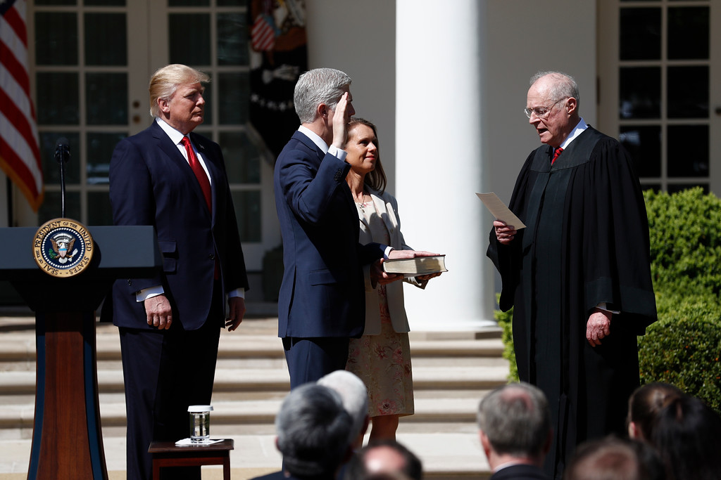 . President Donald Trump watches as Supreme Court Justice Anthony Kennedy administers the judicial oath to Justice Neil Gorsuch during a re-enactment in the Rose Garden of the White House White House in Washington, Monday, April 10, 2017. Holding the bible is Gorsuch\'s wife Marie Louise Gorsuch. (AP Photo/Carolyn Kaster)