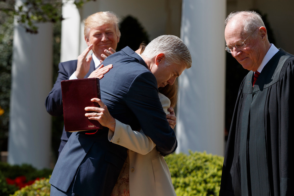 . President Donald Trump applauds as Supreme Court Justice Neil Gorsuch hugs his wife Marie Louise Gorsuch after a swearing in re-enactment ceremony with Supreme Court Justice Anthony Kennedy, right, in the Rose Garden of the White House in Washington, Monday, April 10, 2017. (AP Photo/Evan Vucci)