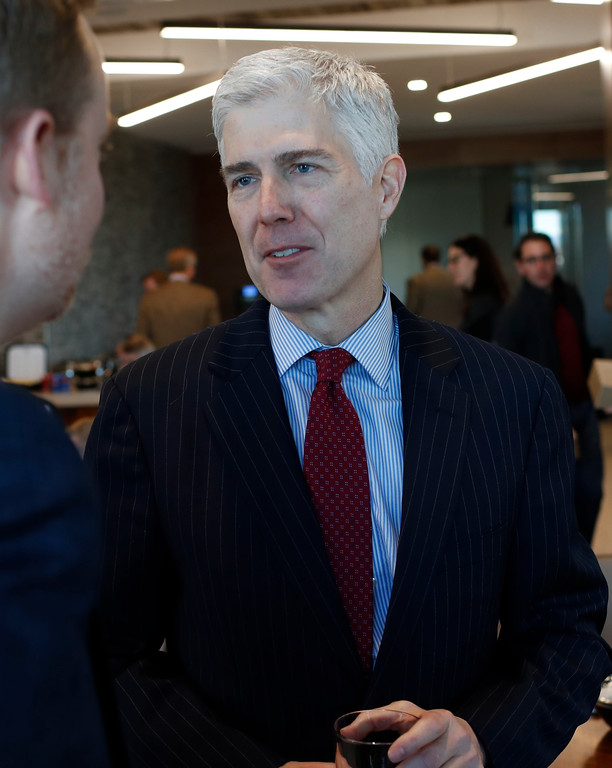 . In this Friday, Jan. 27, 2017, photograph, 10th U.S. Circuit Court of Appeals Judge Neil Gorsuch talks with an attendee after  delivering prepared remarks before a group of attorneys at a luncheon in a legal firm in lower downtown Denver. (AP Photo/David Zalubowski)