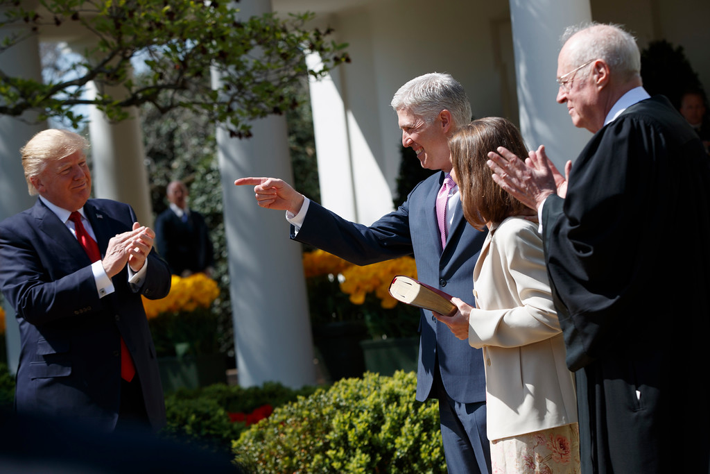 . President Donald Trump applauds after Supreme Court Justice Anthony Kennedy, right, administered the judicial oath to Justice Neil Gorsuch, with wife Marie Louise, in the Rose Garden of the White House in Washington, Monday, April 10, 2017. (AP Photo/Evan Vucci)