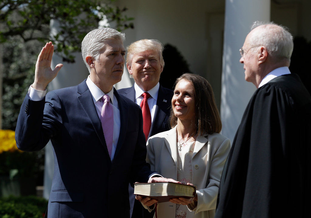 . President Donald Trump watches as Supreme Court Justice Anthony Kennedy administers the judicial oath to Judge Neil Gorsuch during a re-enactment in the Rose Garden of the White House White House in Washington, Monday, April 10, 2017. Holding the bible is Gorsuch\'s wife Marie Louise Gorsuch. (AP Photo/Evan Vucci)