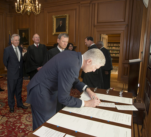 . WASHINGTON, DC - APRIL 10: Justice Neil Gorsuch signs paperwork after Chief Justice John G. Roberts, Jr., administered the Constitutional Oath to the Honorable Neil M. Gorsuch in a private ceremony attended by the Justices of the Supreme Court and members of the Gorsuch family in the Justices Conference Room at the Supreme Court Building on April 10, 2017 in Washington, DC. Gorsuch is the 113th Supreme Court justice. (Photo by Franz Jantzen/Supreme Court of the United States via Getty Images)