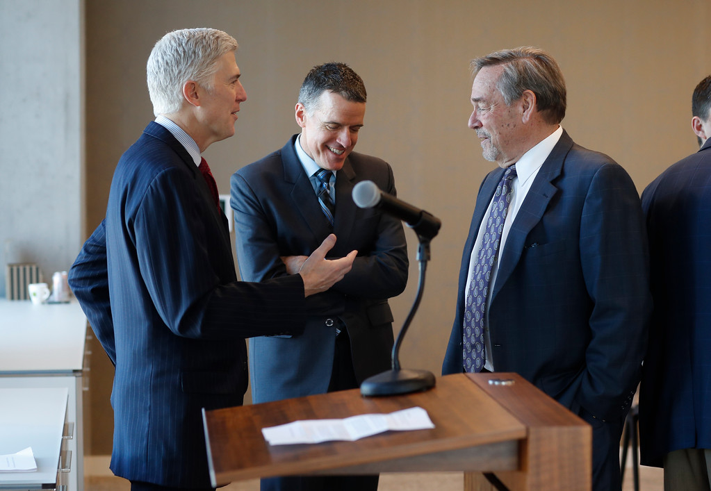 . In this Friday, Jan. 27, 2017, photograph, 10th U.S. Circuit Court of Appeals Judge Neil Gorsuch, left, makes a point while speaking with fellow lawyers before delivering prepared remarks before a group of attorneys at a luncheon in a legal firm in lower downtown Denver. (AP Photo/David Zalubowski)