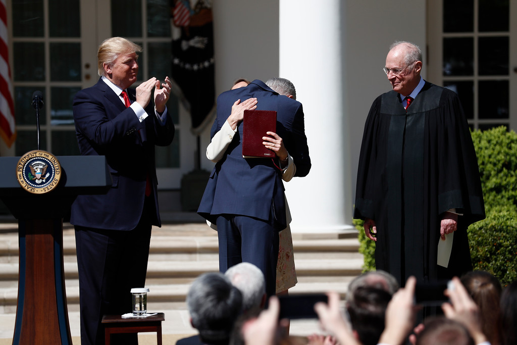 . President Donald Trump watches as Supreme Court Justice Neil Gorsuch hugs his wife Marie Louise in the Rose Garden of the White House White House in Washington, Monday, April 10, 2017, after Supreme Court Justice Anthony Kennedy, right, administered a public oath of office to Gorsuch.  (AP Photo/Carolyn Kaster)