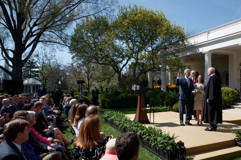 . President Donald Trump watches as Supreme Court Justice Anthony Kennedy administers the judicial oath to Justice Neil Gorsuch, accomp[anied by his wife Marie Louise, during a re-enactment in the Rose Garden of the White House in Washington, Monday, April 10, 2017. (AP Photo/Evan Vucci)