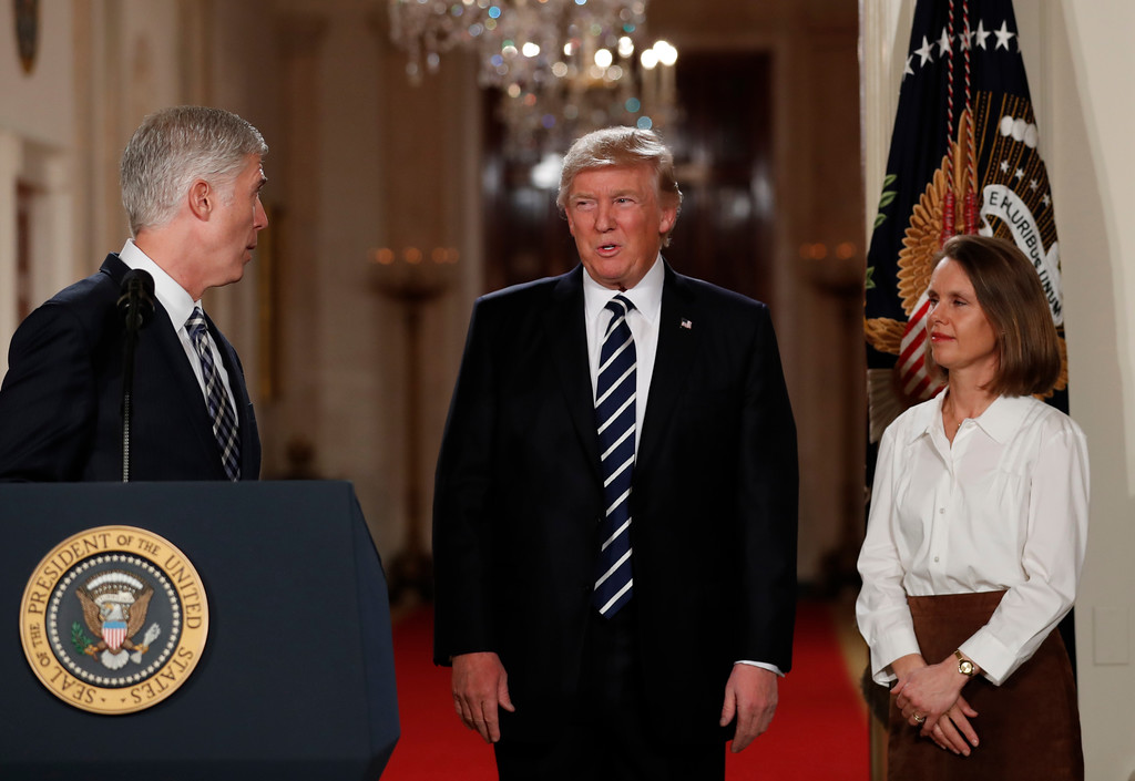 . Judge Neil Gorsuch turns to look at President Donald Trump in the East Room of the White House in Washington, Tuesday, Jan. 31, 2017, after Trump announced Gorsuch as his nominee for the Supreme Court. Gorsuch\'s wife Louise watches. (AP Photo/Carolyn Kaster)