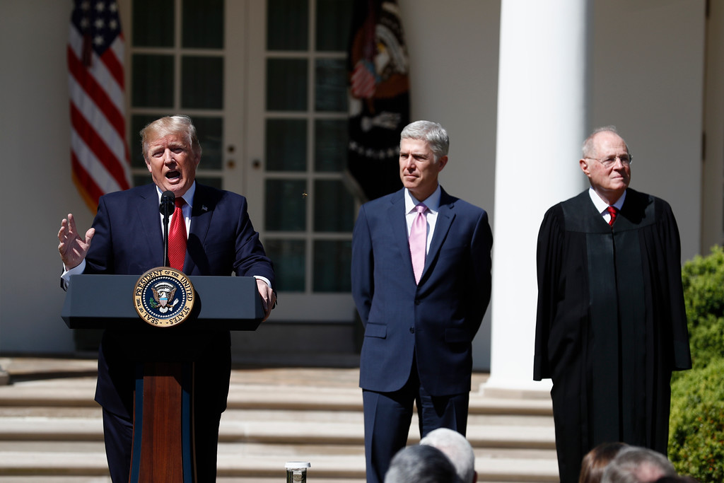 . President Donald Trump, accompanied by Supreme Court Justice Anthony Kennedy, right, and Justice Neil Gorsuch speaks in the Rose Garden of the White House White House in Washington, Monday, April 10, 2017, before a public swearing-in ceremony for Gorsuch. (AP Photo/Carolyn Kaster)