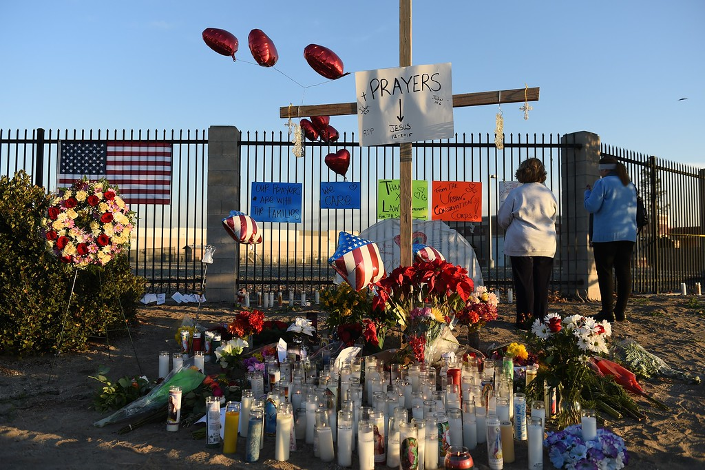 ". People pray at a makeshift memorial for the victims of a mass shooting near the Inland Regional Center in San Bernardino, California on December 4, 2015. The FBI said the mass shooting in California was being investigated as ""an act of terrorism,\"" amid reports the female assailant had pledged allegiance to the Islamic State group online. Syed Farook, 28, and his 27-year-old wife Tashfeen Malik died in a shootout with police, hours after killing 14 people at a year-end party organized by Farook\'s employer in San Bernardino.  AFP PHOTO / ROBYN BECK / AFP / ROBYN BECK        (Photo credit should read ROBYN BECK/AFP/Getty Images)"