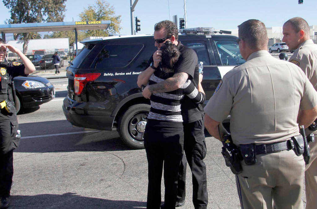 . A couple from Inland Valley Regional Facility for the Mentally Disable hug as they meet on Waterman Avenue, after shooter shot as many as 20 people at the Inland Valley Regional Facility in San Bernardino, CA., Wednesday, December 2, 2015. (Photo by James Carbone for the SAn Bernardino Sun)