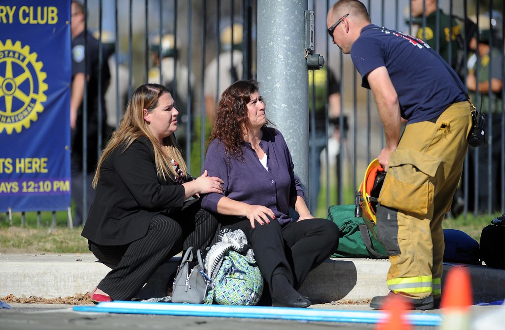 . Two women speak with a firefighter at the triage area near where an active shooter situation is taking place at the Inland Regional Center on Wednesday, December 2, 2015, San Bernardino, Ca.  (Micah Escamilla/The Sun)
