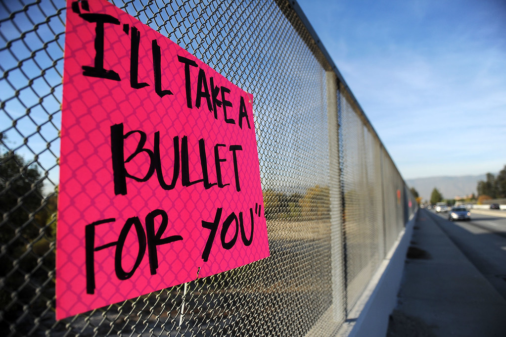 ". A sign stating, ""I\'ll take a bullet for you,\"" paraphrasing San Bernardino County Sheriff Det. Jorge Lozano\'s statement as he lead people to safety during last week\'s mass shooting, hangs on a fence along Waterman Avenue near the scene of the shooting on Wednesday, December 9, 2015 in San Bernardino, Ca. (Micah Escamilla/The Sun)"